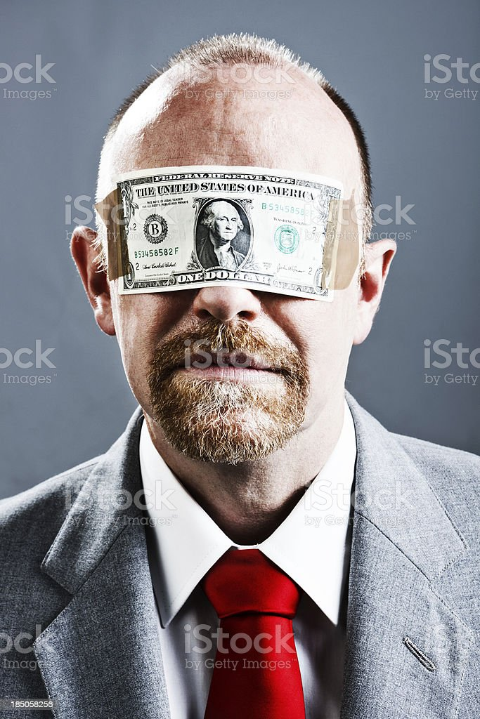 Serious businessman blinded by US dollar bill stock photo