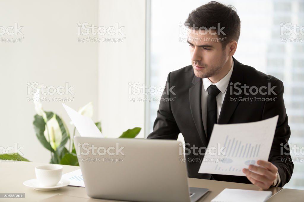 Serious businessman holding financial report, analyzing project stats, company growth stock photo