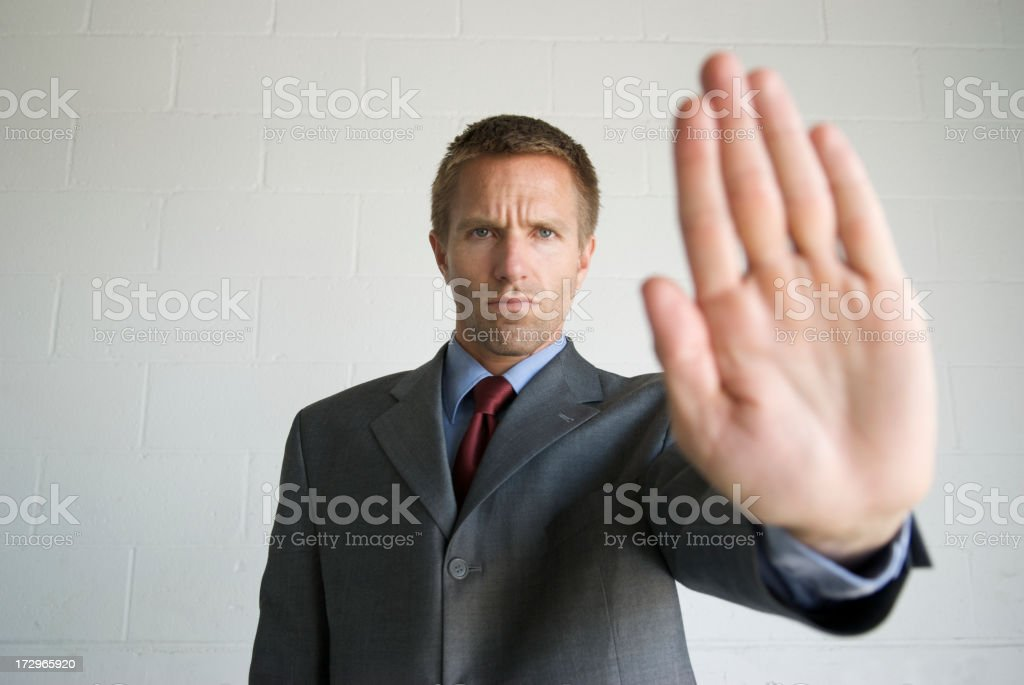 Serious Businessman Holds Hand Out as Stop Sign royalty-free stock photo