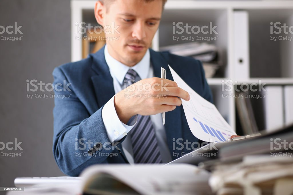 Serious businessman in the office examines documents royalty-free stock photo