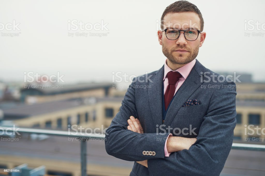 Serious businessman leaning against railing stock photo