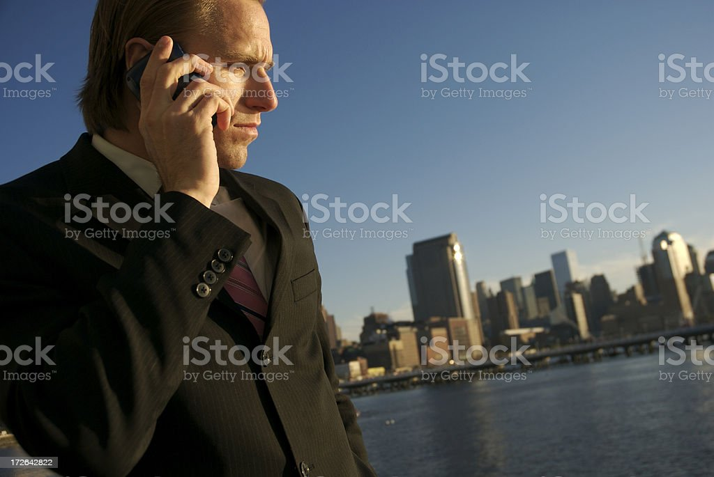 Serious Businessman Listening on Mobile Phone Outdoors City Skyline royalty-free stock photo