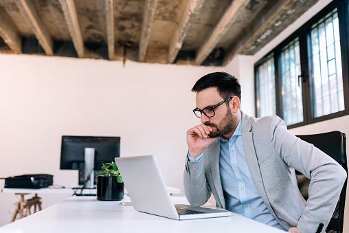 istock Serious businessman looking at laptop screen. 964369224