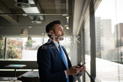 Serious businessman looking through the window