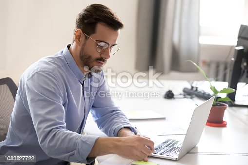 istock Serious businessman making notes at workplace 1083827722