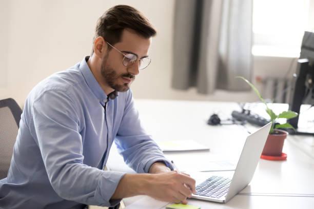 serious businessman making notes at workplace - carta documento imagens e fotografias de stock
