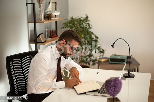 1083827722 istock photo Serious businessman making notes at workplace 1210049187