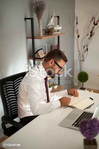 1083827722 istock photo Serious businessman making notes at workplace 1210049188