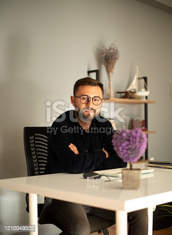 1083827722 istock photo Serious businessman making notes at workplace 1210049322