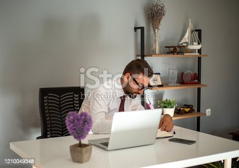1083827722 istock photo Serious businessman making notes at workplace 1210049348