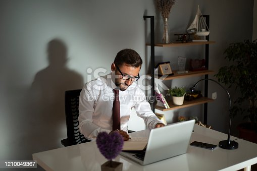 1083827722 istock photo Serious businessman making notes at workplace 1210049367