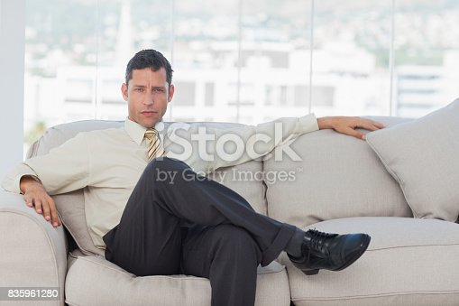 530281723istockphoto Serious businessman posing sitting on sofa 835961280