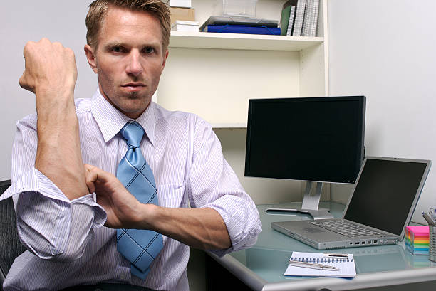 Serious Businessman Rolling up his Sleeves in Office Cubicle stock photo