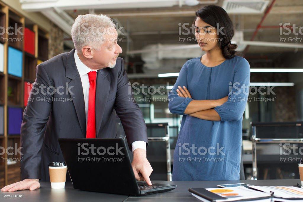 Serious businessman showing presentation on laptop stock photo