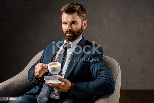 1081599130 istock photo serious businessman showing white cup with coffee while sitting in armchair 1081599142