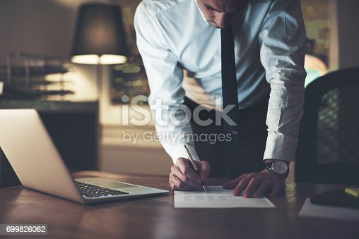 istock Serious businessman signing contract 699826062