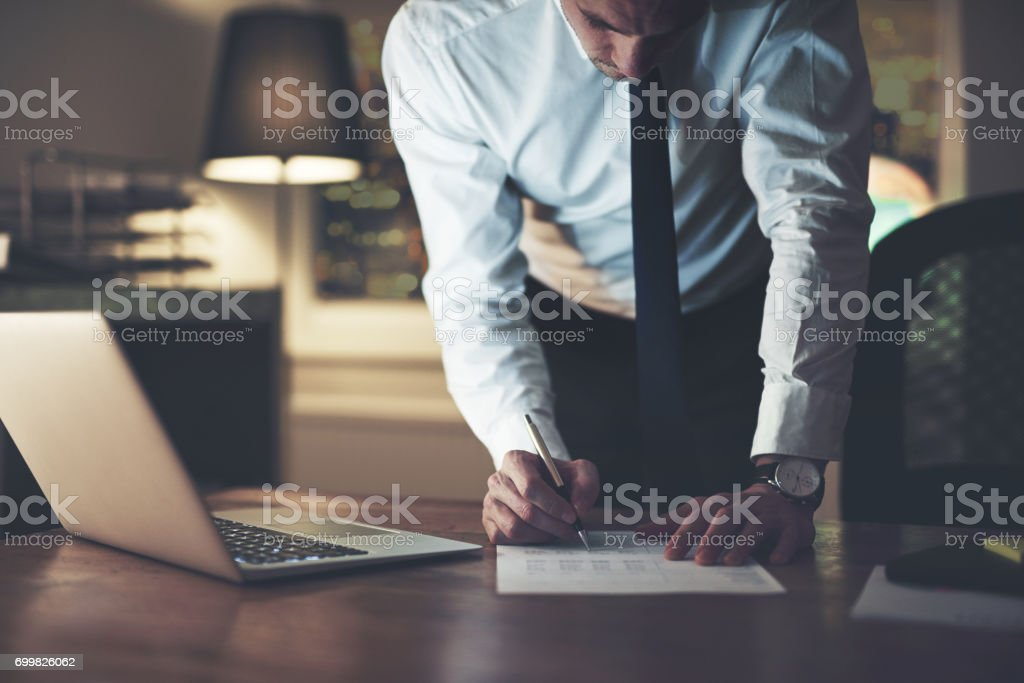 Serious businessman signing contract stock photo