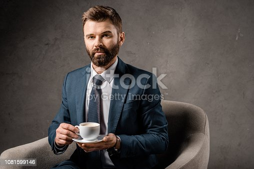 1081599130 istock photo serious businessman sitting in armchair with cup of coffee 1081599146