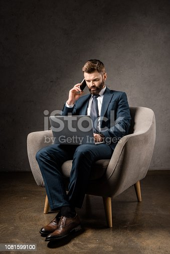 istock serious businessman sitting in beige armchair and using digital devices 1081599100