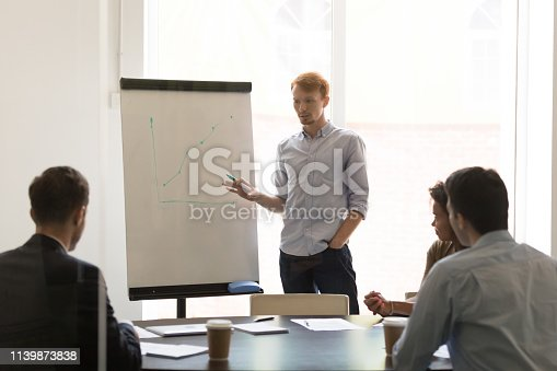 1031235468 istock photo Serious businessman speaker giving flip chart presentation explaining sales growth 1139873838