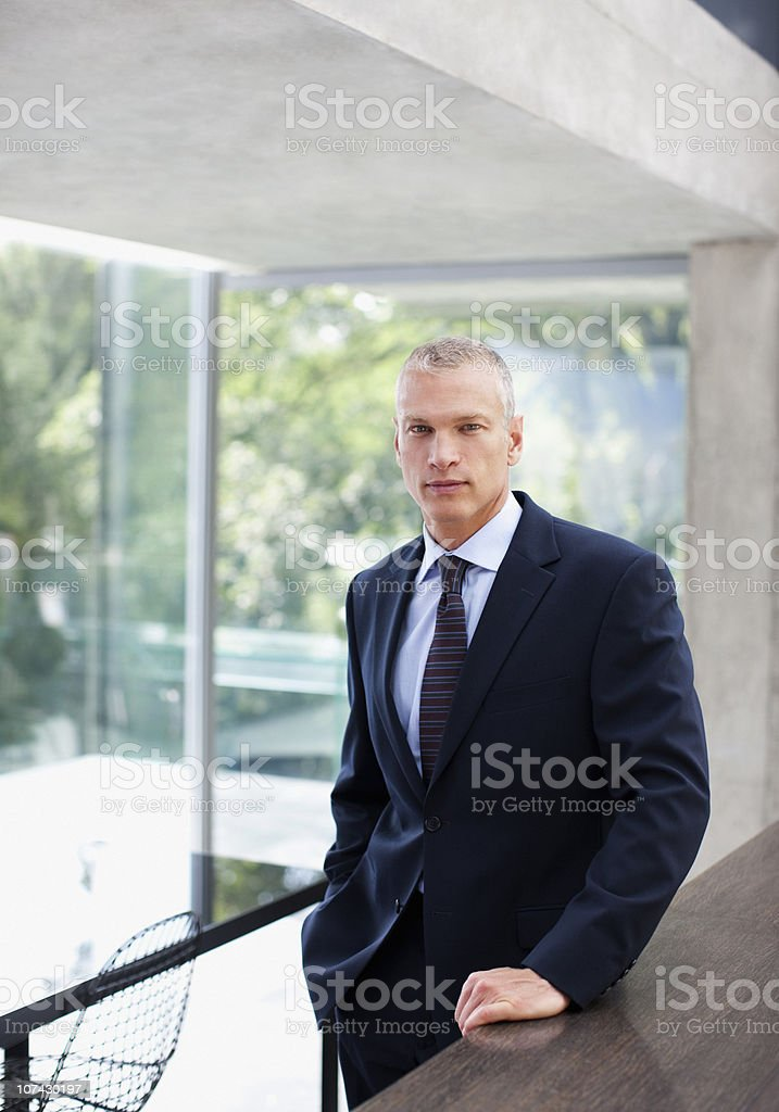 Serious businessman standing at counter in conference room stock photo
