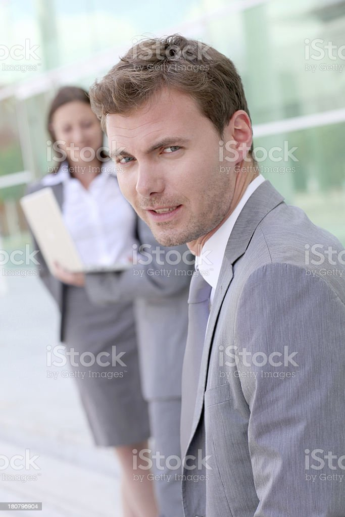 Serious businessman standing in front of modern building royalty-free stock photo