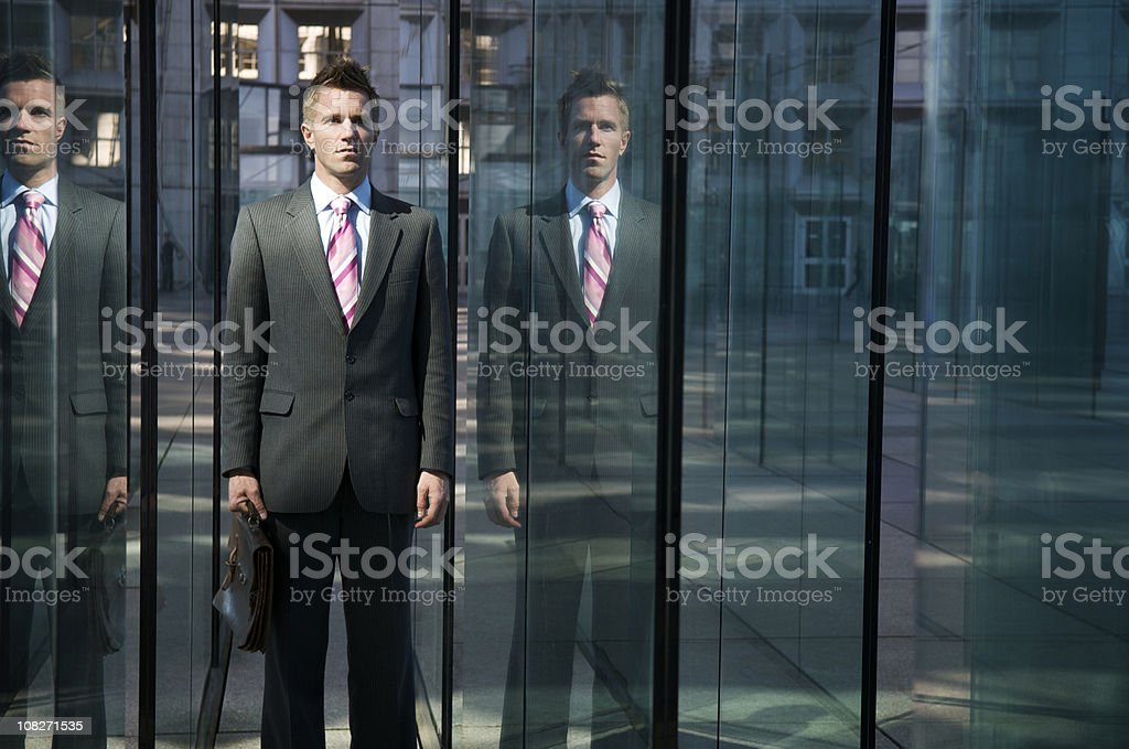 Serious Businessman Standing with Reflections in Modern City Glass royalty-free stock photo