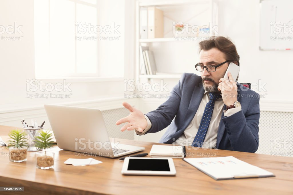 Serious businessman talking on mobile phone royalty-free stock photo