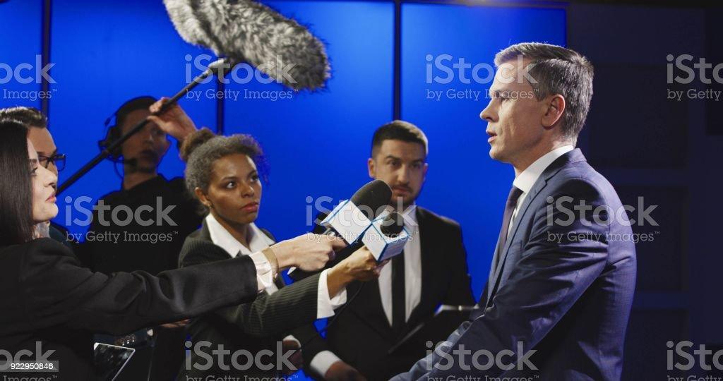 Serious businessman talking to mass media representatives stock photo