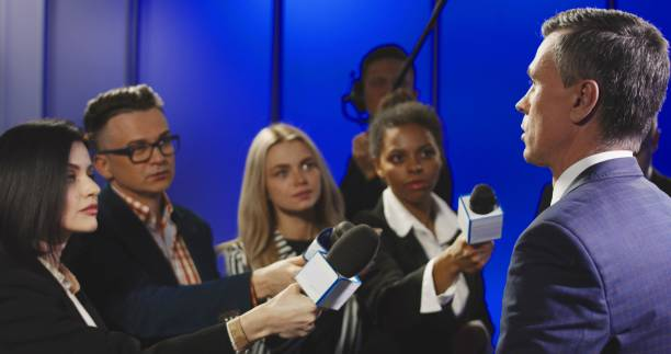 Serious businessman talking to mass media representatives Big group of multiracial journalists with microphones and other technological equipment having interview with middle-aged politician in underlit studio. spokesperson stock pictures, royalty-free photos & images