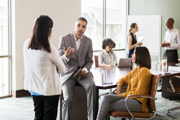Serious businessman talking with associates Concerned businessman gestures as he talks with associates about an issue. governing board stock pictures, royalty-free photos & images