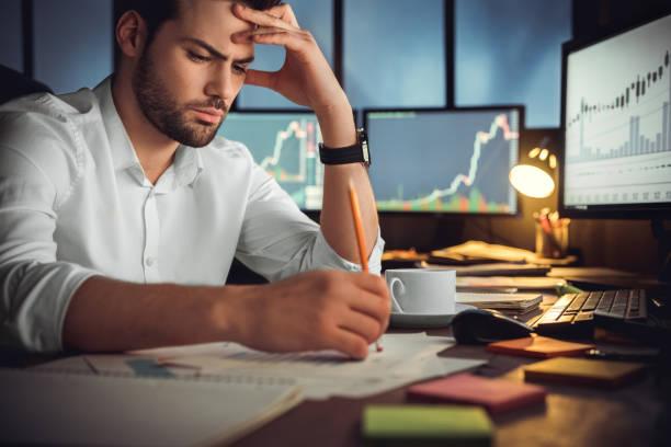 seriöser geschäftsmann denkt an problemlösung, die spät im amt arbeitet - börsenhandel finanzberuf stock-fotos und bilder