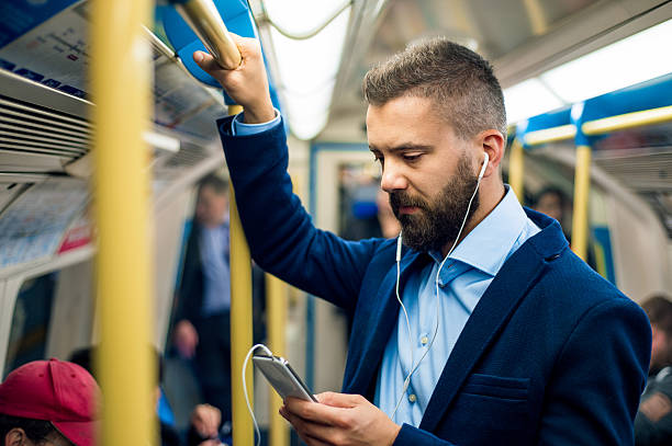 Serious businessman travelling to work. Standing inside undergro Serious businessman with headphones travelling to work. Standing inside underground wagon, holding handhandle. underground stock pictures, royalty-free photos & images