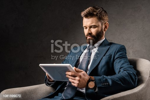 1081599130 istock photo serious businessman using digital tablet and sitting in armchair 1081599070