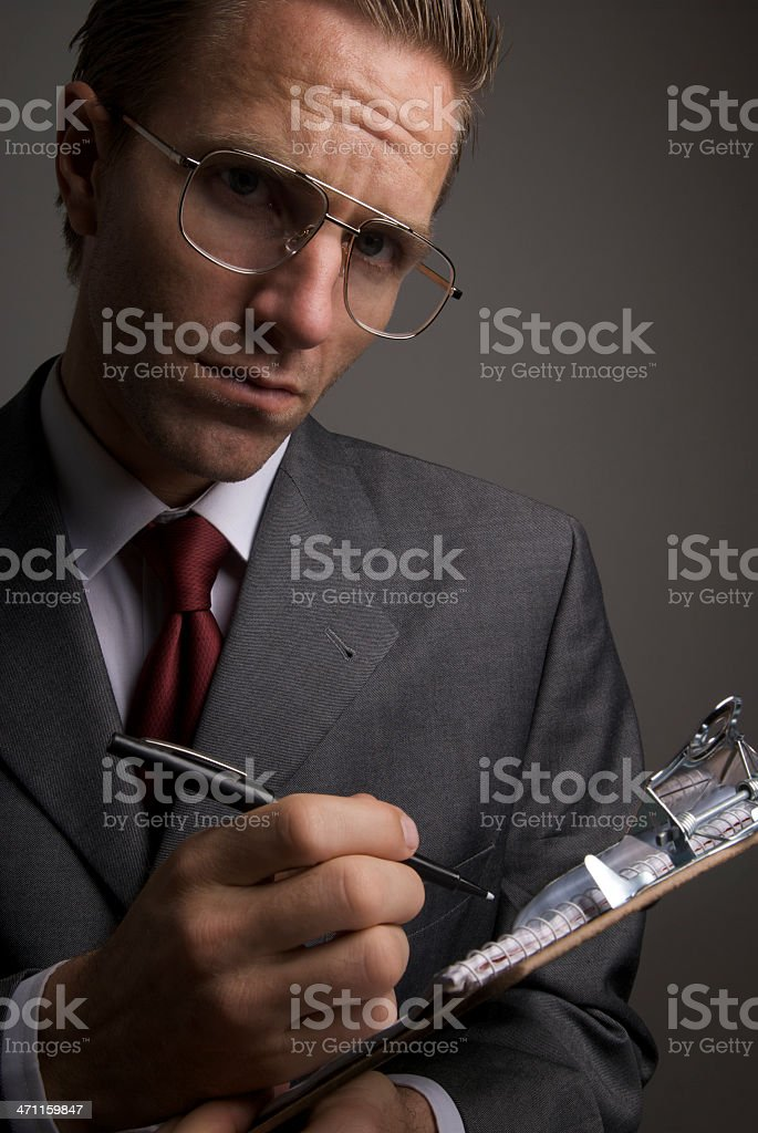 Serious Businessman with Glasses Taking Notes on Clipboard royalty-free stock photo