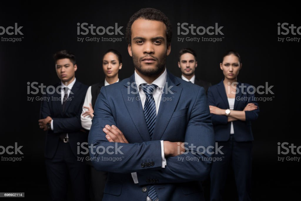 Serious businessman with his business colleagues standing with arms crossed and looking at camera isolated on black stock photo