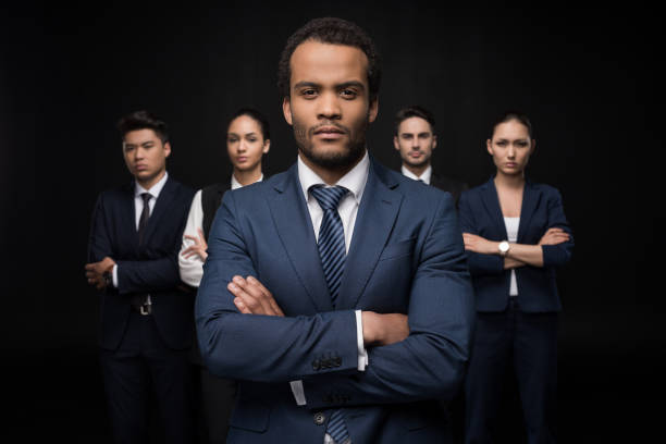 Serious businessman with his business colleagues standing with arms crossed and looking at camera isolated on black - foto stock
