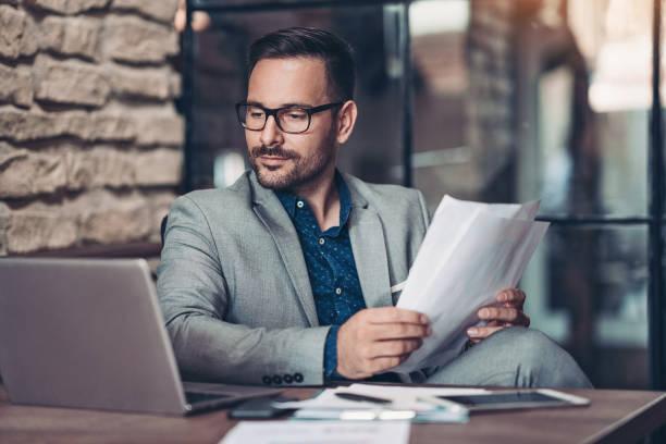Seriöser Geschäftsmann mit Laptop und Dokumenten – Foto