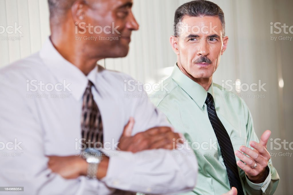 Serious businessman with smiling colleague royalty-free stock photo