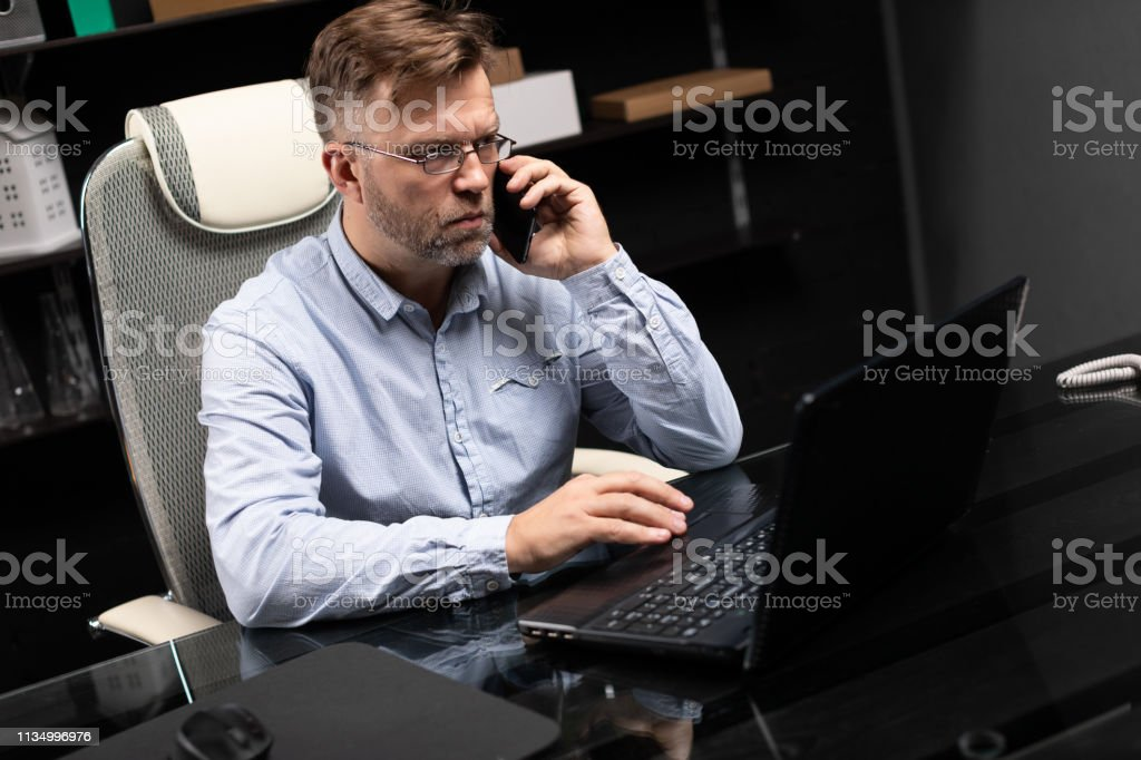 Serious businessman working on a laptop and talking on a mobile phone modern man works in stylish office behind laptop and holds black mobile phone in his hand. Portrait of businessman at work. Agent with mobile phone in his hands working at computer Administrator Stock Photo