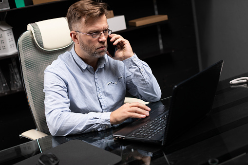 Serious Businessman Working On A Laptop And Talking On A Mobile Phone Stock Photo - Download Image Now
