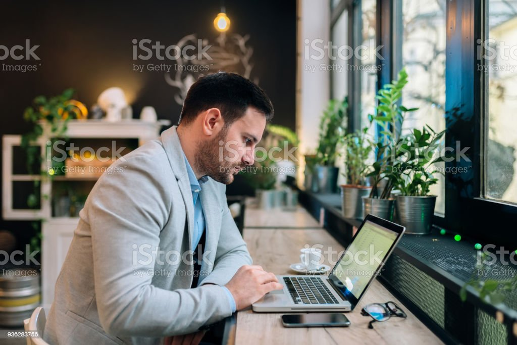 Serious businessman working on a laptop at the cafe. royalty-free stock photo