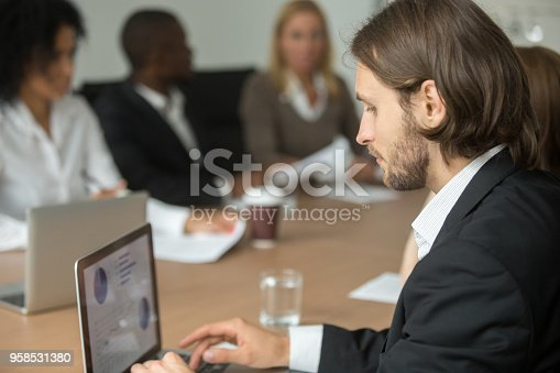 958531418 istock photo Serious businessman working on laptop online at diverse group meeting 958531380