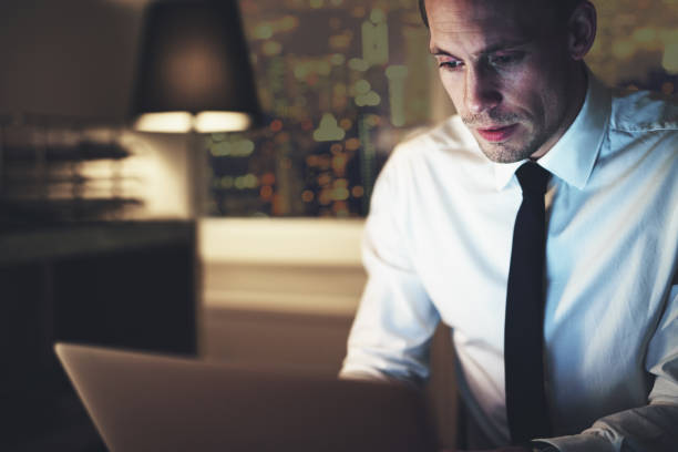 serious businessman working on laptop - paralegal stock photos and pictures