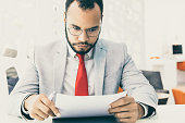 Serious businessman working with papers. Focused young African American businessman in eyeglasses sitting at table and holding documents in office. Paperwork concept