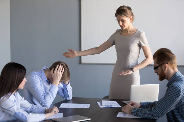 Serious businesswoman ask failed employee to leave meeting stock photo