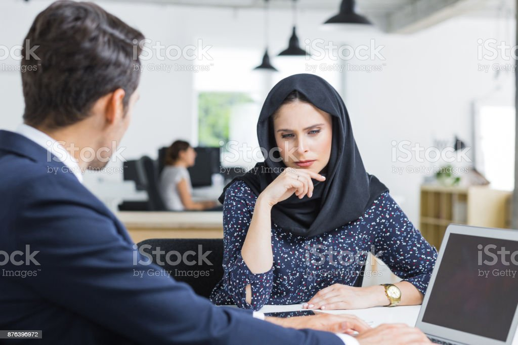 Serious businesswoman at desk with male colleague Serious businesswoman at desk with male colleague sitting by and working on laptop. Muslim businesswoman thinking while working with male partner in office. 20-29 Years Stock Photo