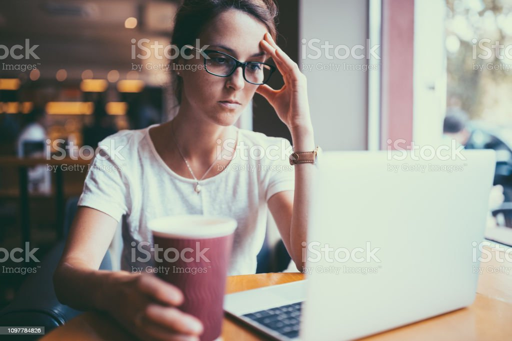 Worried businesswoman in cafe using laptop to read news event