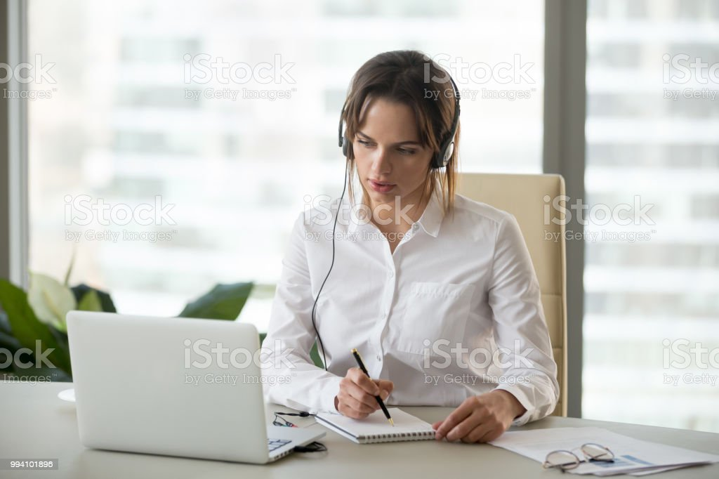 Serious businesswoman in headphones watching webinar on laptop making notes stock photo