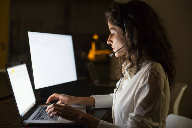 Serious businesswoman in headset using laptop stock photo